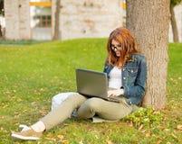 Adolescente sonriente en lentes con el ordenador portátil Fotos de archivo