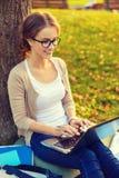 Adolescente sonriente en lentes con el ordenador portátil Imágenes de archivo libres de regalías
