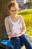Adolescente sonriente en lentes que escribe en cuaderno Imagen de archivo