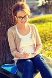 Adolescente sonriente en lentes que escribe en cuaderno Foto de archivo libre de regalías