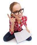Adolescente sonriente en libro de lectura de las lentes Imagen de archivo
