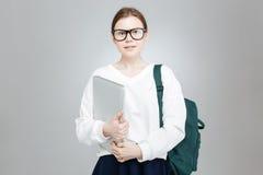 Adolescente sonriente en los vidrios que sostienen la mochila y el ordenador portátil verdes Foto de archivo libre de regalías