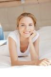 Adolescente sonriente en una cama Imagen de archivo libre de regalías