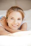 Adolescente sonriente en una cama Imagenes de archivo