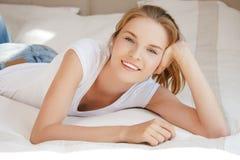 Adolescente sonriente en una cama Fotos de archivo libres de regalías