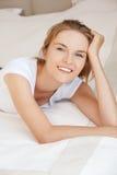 Adolescente sonriente en una cama Fotografía de archivo libre de regalías