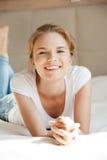 Adolescente sonriente en una cama Fotos de archivo