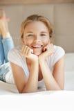 Adolescente sonriente en una cama Imágenes de archivo libres de regalías