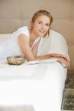 Adolescente sonriente en una cama con palomitas Imágenes de archivo libres de regalías