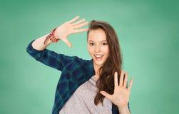 Adolescente sonriente feliz del estudiante que muestra las manos Fotografía de archivo libre de regalías