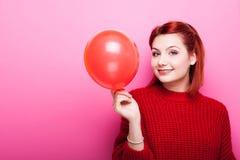 Adolescente sonriente feliz en el suéter rojo que sostiene un globo rojo en h Imágenes de archivo libres de regalías