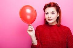 Adolescente sonriente feliz en el suéter rojo que sostiene un globo rojo en h Fotografía de archivo
