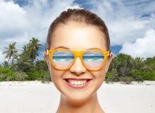 Adolescente sonriente feliz en sombras sobre la playa Imagen de archivo libre de regalías