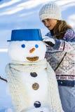 Adolescente sonriente feliz que juega con un muñeco de nieve Fotos de archivo libres de regalías