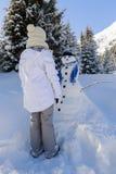 Adolescente sonriente feliz que juega con un muñeco de nieve Imagen de archivo