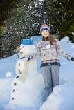Adolescente sonriente feliz que juega con un muñeco de nieve Fotografía de archivo