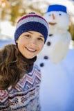 Adolescente sonriente feliz que juega con un muñeco de nieve Imagen de archivo libre de regalías