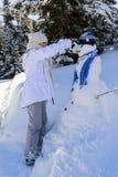 Adolescente sonriente feliz que juega con un muñeco de nieve en un triunfo nevoso Imágenes de archivo libres de regalías
