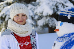 Adolescente sonriente feliz que juega con un muñeco de nieve en un triunfo nevoso Fotografía de archivo libre de regalías