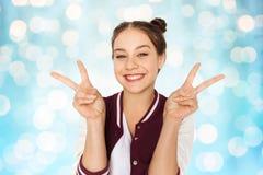 Adolescente sonriente feliz que muestra el signo de la paz Fotos de archivo