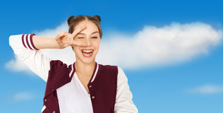 Adolescente sonriente feliz que muestra el signo de la paz Fotografía de archivo