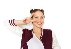 Adolescente sonriente feliz que muestra el signo de la paz Foto de archivo libre de regalías