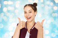 Adolescente sonriente feliz que muestra los pulgares para arriba Imagen de archivo