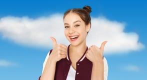 Adolescente sonriente feliz que muestra los pulgares para arriba Imagenes de archivo