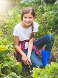 Adolescente sonriente feliz que planta lechuga en el jardín en d soleada Foto de archivo