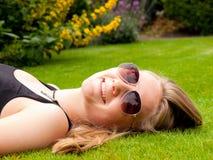 Adolescente sonriente hermoso con las gafas de sol que mienten en ella detrás Imagenes de archivo