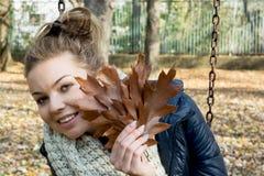 Adolescente sonriente hermoso con las hojas del roble marrón Fotos de archivo libres de regalías