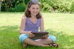 Adolescente sonriente hermoso con PC de la tableta, al aire libre Fotografía de archivo