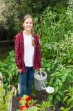 Adolescente sonriente hermoso en las botas de goma con la regadera que trabaja en jardín Foto de archivo libre de regalías