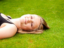 Adolescente sonriente hermoso que miente en ella detrás en GR verde Fotografía de archivo