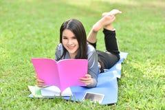 Adolescente sonriente hermoso que miente en hierba y el libro leído Imágenes de archivo libres de regalías