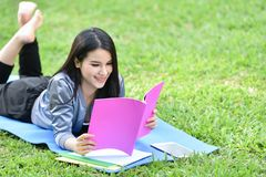 Adolescente sonriente hermoso que miente en hierba y el libro leído Imagen de archivo libre de regalías