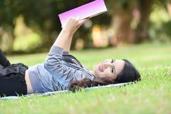 Adolescente sonriente hermoso que miente en hierba y el libro leído Foto de archivo libre de regalías