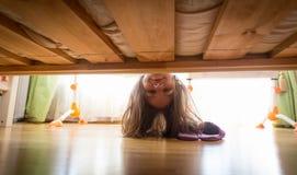 Adolescente sonriente hermoso que mira debajo de la cama para el deslizador Imágenes de archivo libres de regalías