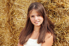 Adolescente sonriente hermoso que se sienta cerca de una bala de heno Foto de archivo