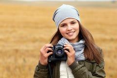 Adolescente sonriente hermoso que sostiene la cámara de la foto del vintage Imagenes de archivo