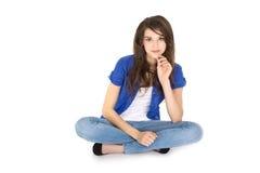 Adolescente sonriente joven aislado que se sienta con las piernas cruzadas. Imagen de archivo libre de regalías