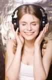 Adolescente sonriente lindo en auriculares que escucha Fotografía de archivo libre de regalías