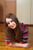 Adolescente sonriente lindo que miente en el suelo Foto de archivo libre de regalías