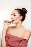 Adolescente sonriente precioso que come el chocolate Fotos de archivo