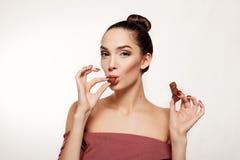 Adolescente sonriente precioso que come el chocolate Imagen de archivo libre de regalías