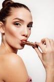 Adolescente sonriente precioso que come el chocolate Imagen de archivo