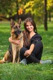 Adolescente sonriente que abraza un perro Imagen de archivo