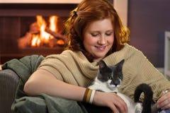 Adolescente sonriente que ama su gato en casa Fotos de archivo libres de regalías