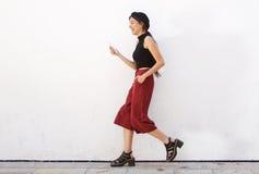 Adolescente sonriente que camina y que lee el texto en el teléfono móvil Fotos de archivo