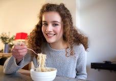 Adolescente sonriente que come la comida en casa Imagen de archivo